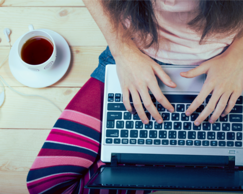 Girl using a laptop with a full coffee mug and headphones placed on her right side