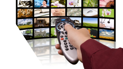 Man's right hand pointing remote towards multiple displays