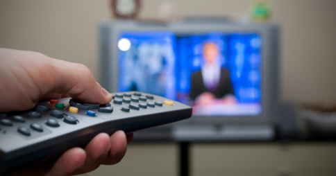 Left hand pointing remote control towards TV. Image credit: flash.pro via Flickr
