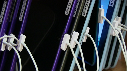 Row of iPads with numbered labels, all connected via 30-pin USB cables